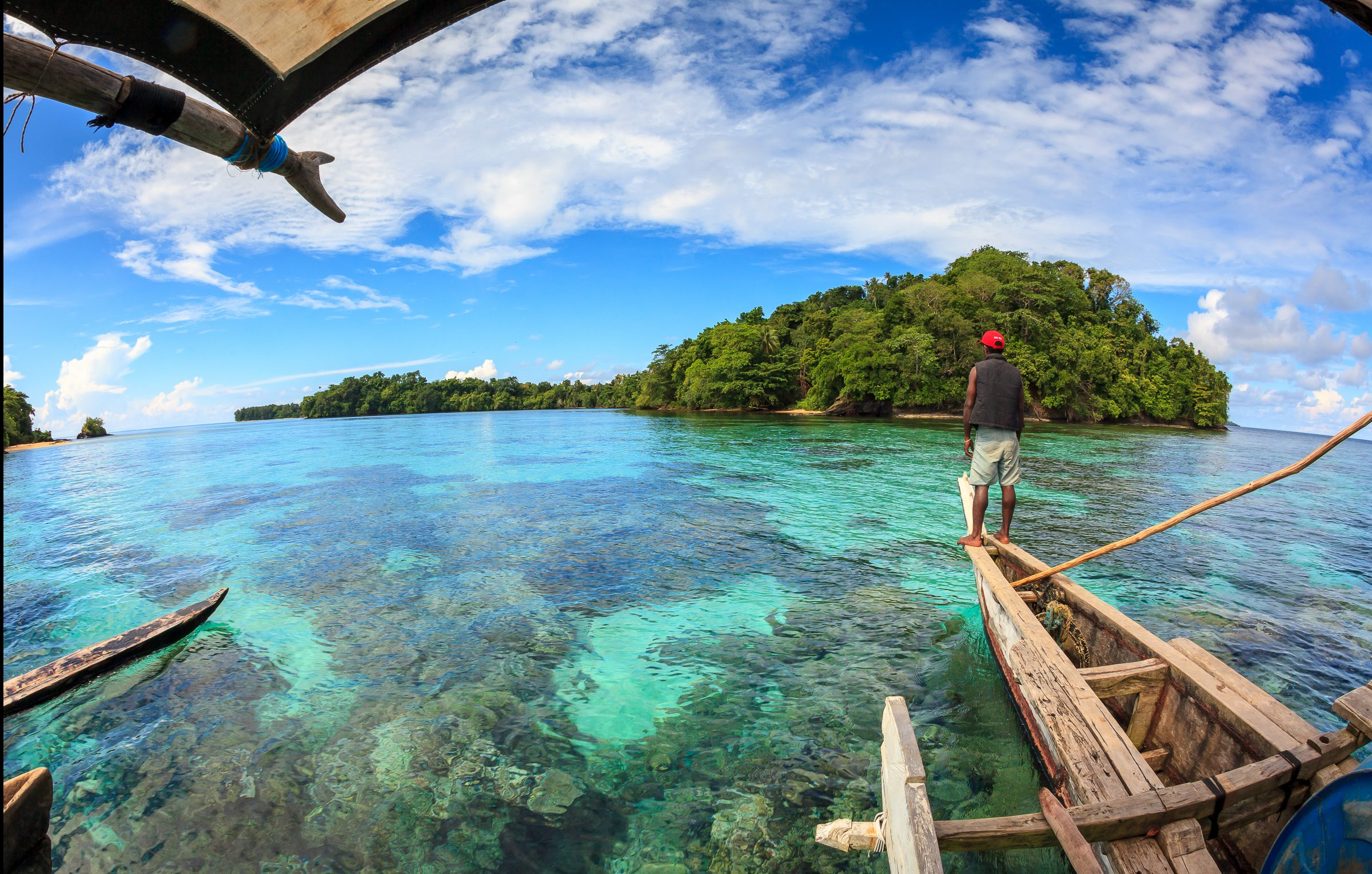 "A Titan villager navigates a traditional melanesian outrigger over shallow corals that flank a small island in the Manus Province of Papua New Guinea. Mystery shrouds the densely vegetated island, as legend amongst the indigenous Mbuke people maintains that it is home to a ""dinosaur"" that has never been seen on any other island in the Archipeligo."