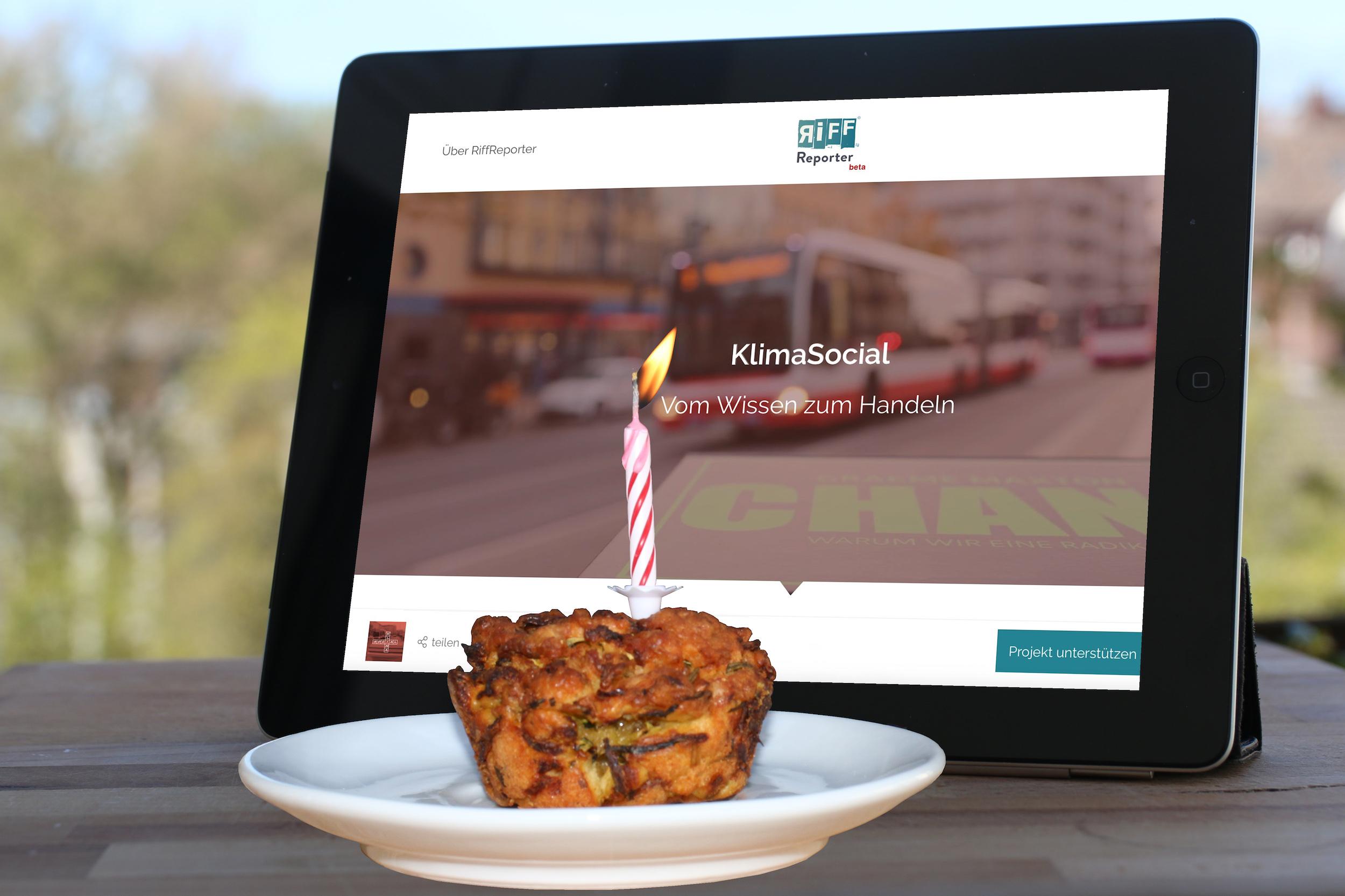 Ein Törtchen mit einer Geburtstagskerze steht vor einem iPad. Auf dem Bildschirm ist die Startseite der Koralle KlimaSocial zu sehen mit dem Motto: Vom Wissen zum Handeln.